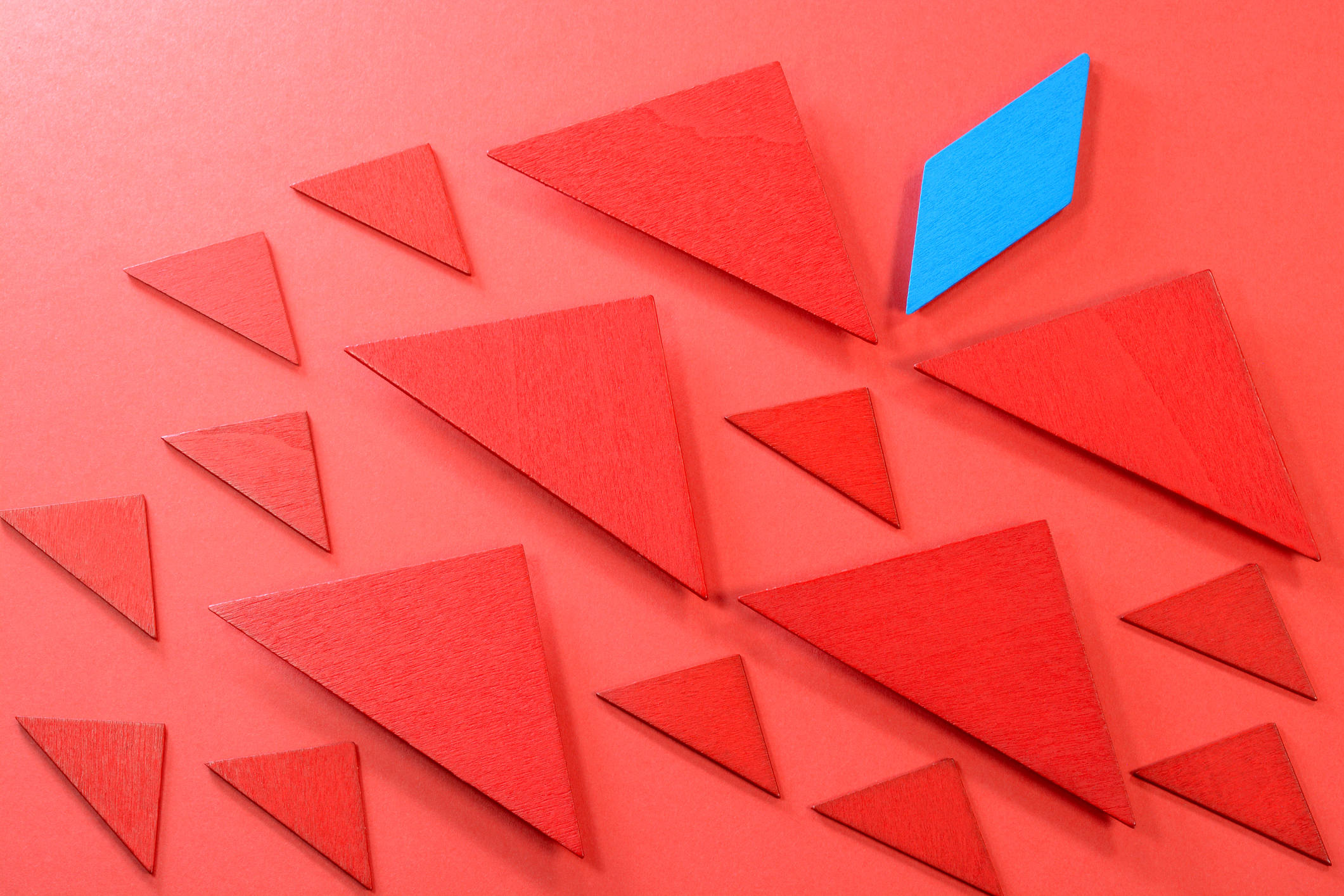 Blue rectangular wooden piece leading the other red wooden pieces