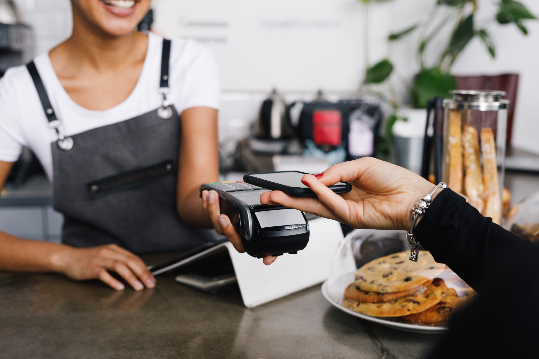Customer using mobile phone for contactless payment at a cafe
