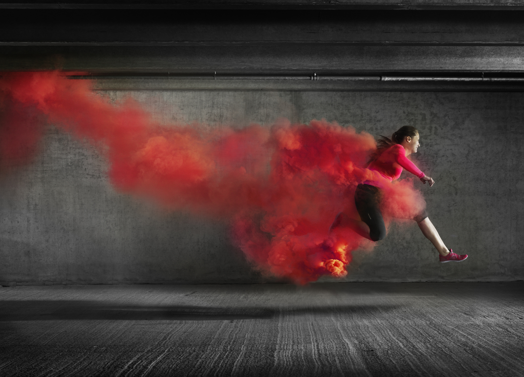 Female athlete leaping through red smoke