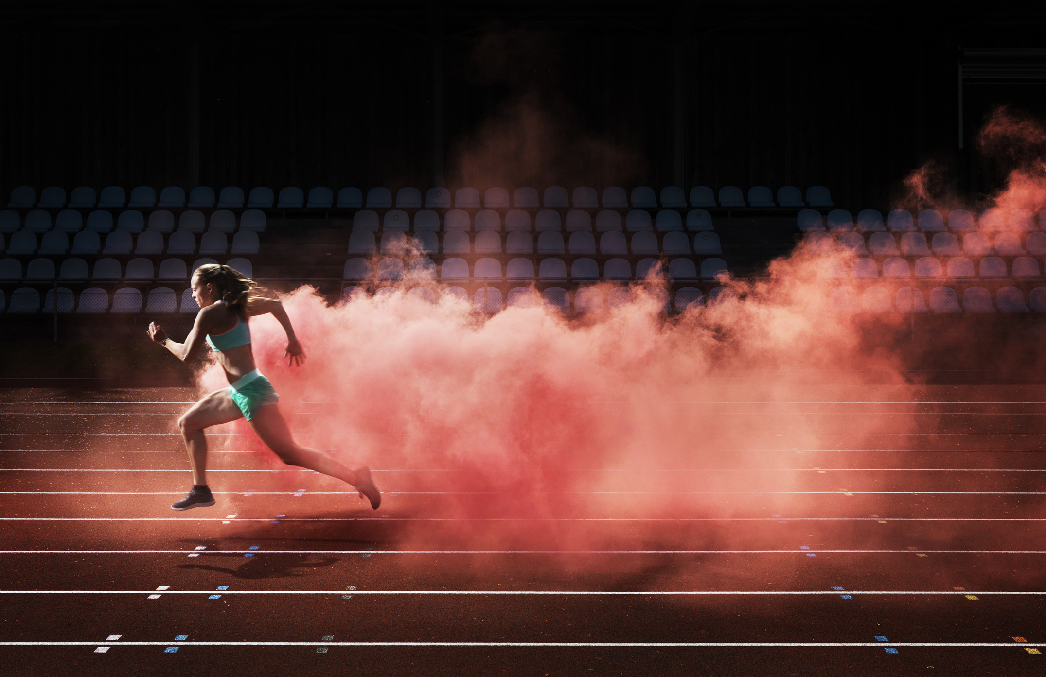 Female athlete unning on a race track and leaving behind a trail of red smoke