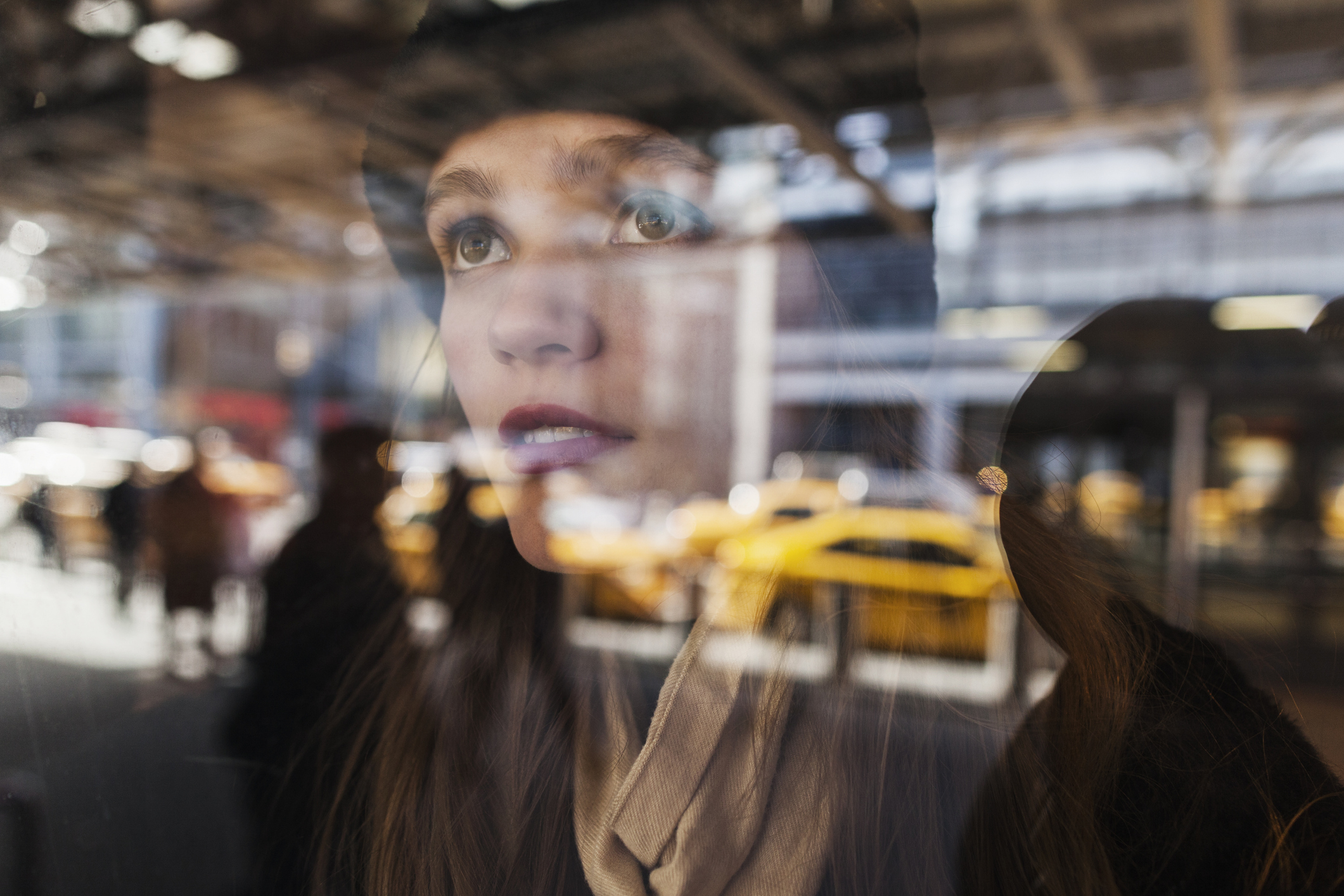 Girl looks through a glass window at taxis and people in New York City