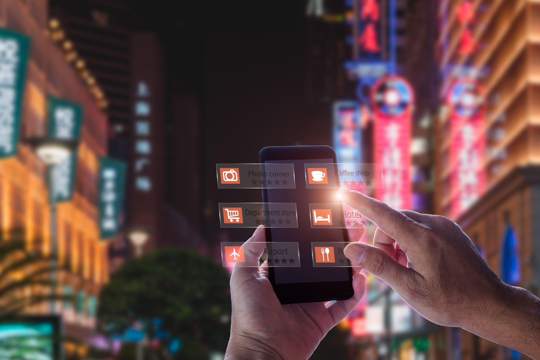 Hand holding smart phone using an AR application in the middle of a street at night