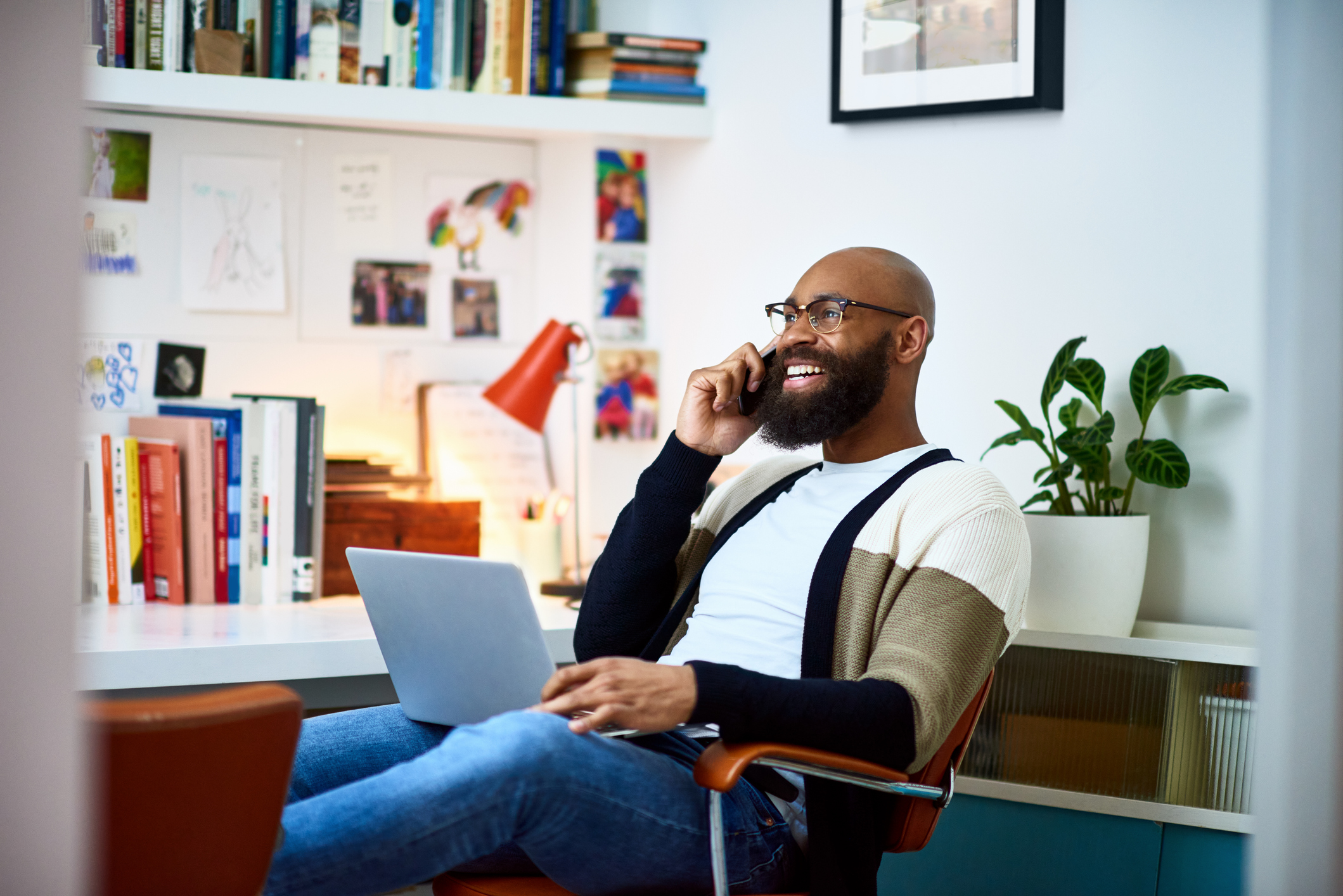 Man sitting on chair with laptop on phone call