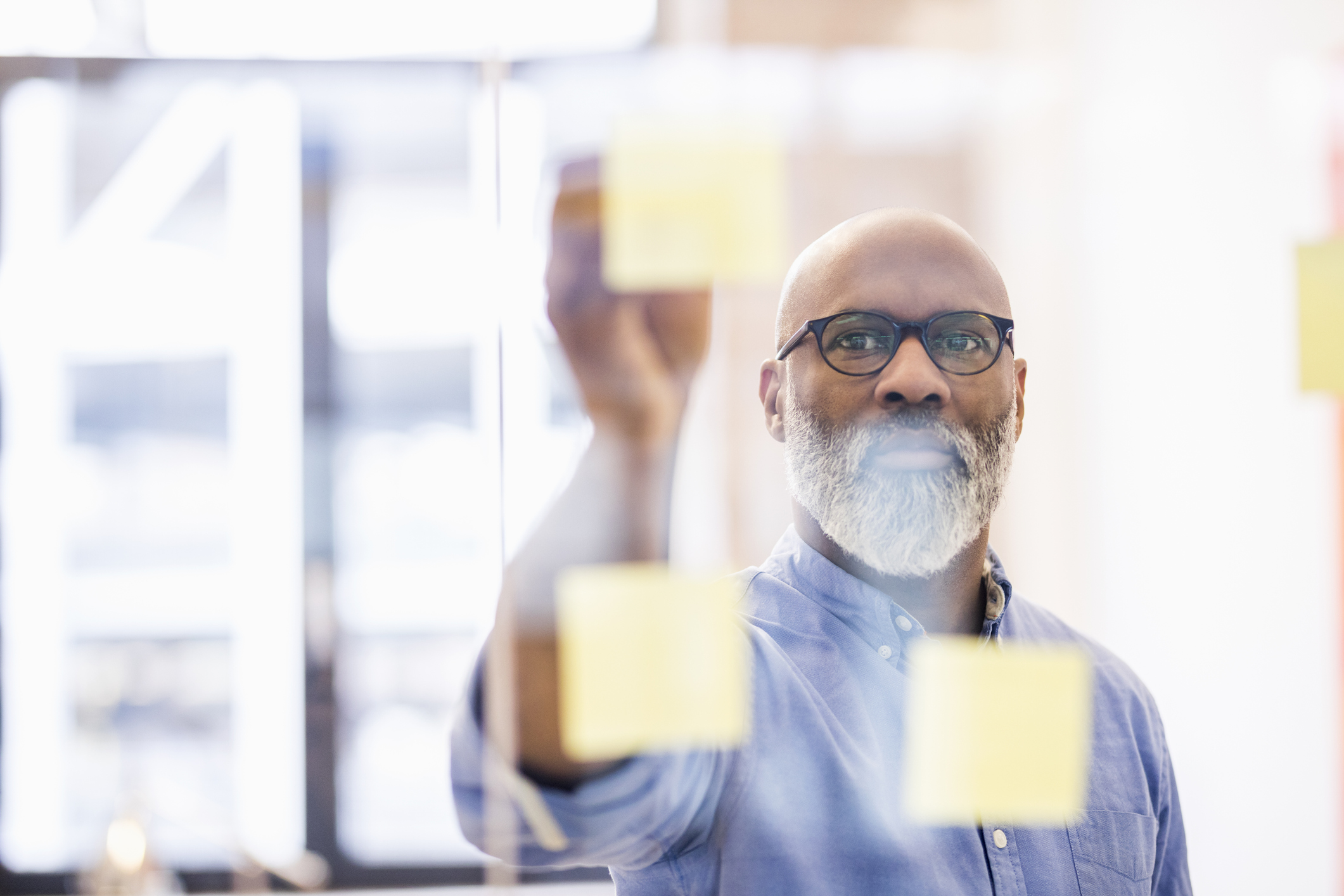 Man taking adhesive note from glass wall in office