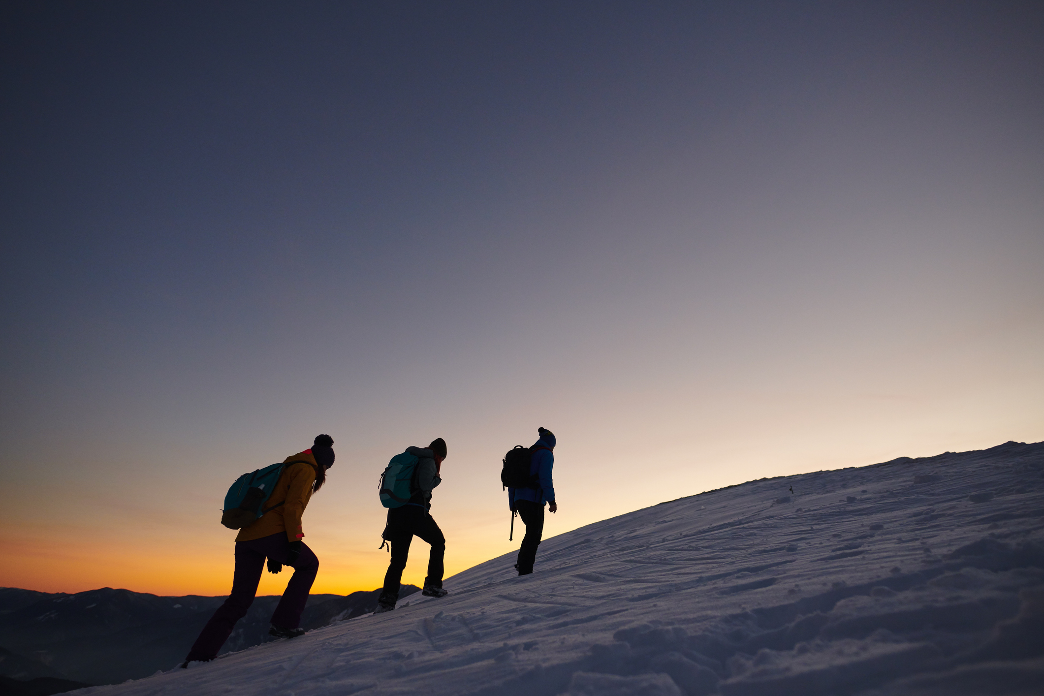 Three persons in cold winter day moving up on the snowy mountains