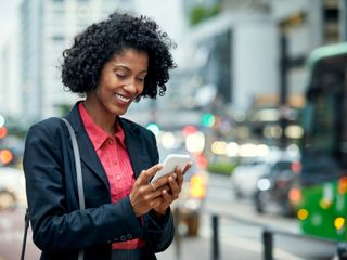 Woman smiling and holding a phone on a street
