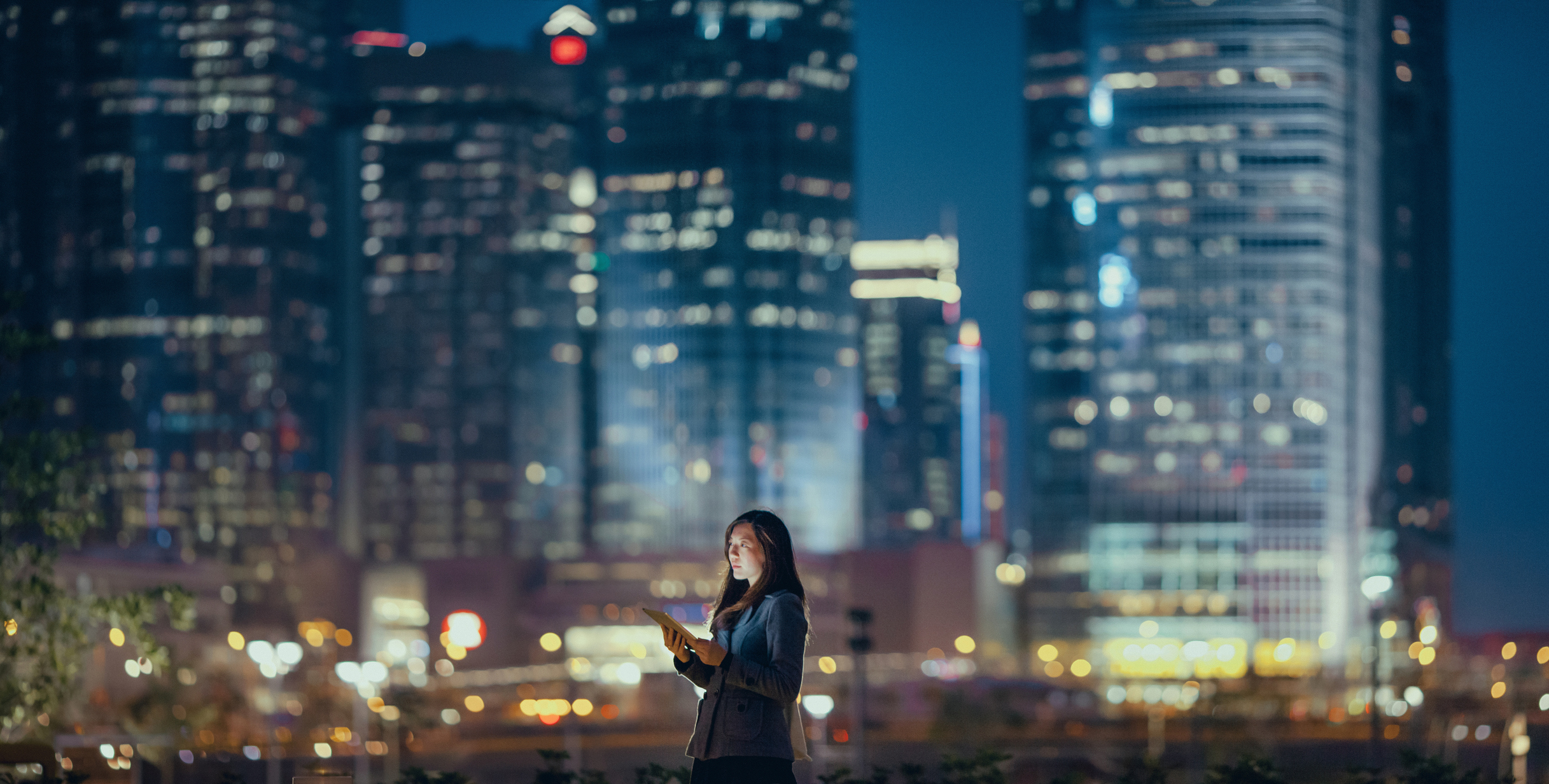 Woman using digital tablet against illuminated corporate skyscrapers at night