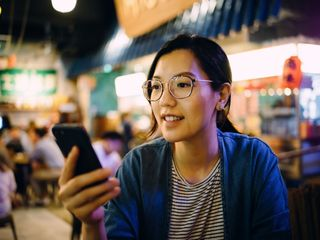Woman using smartphone in a traditional style restaurant