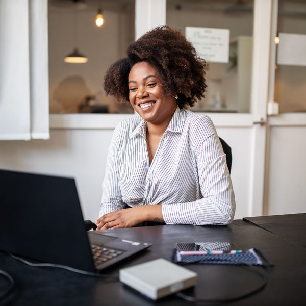 Woman sitting in office smiling during a video call