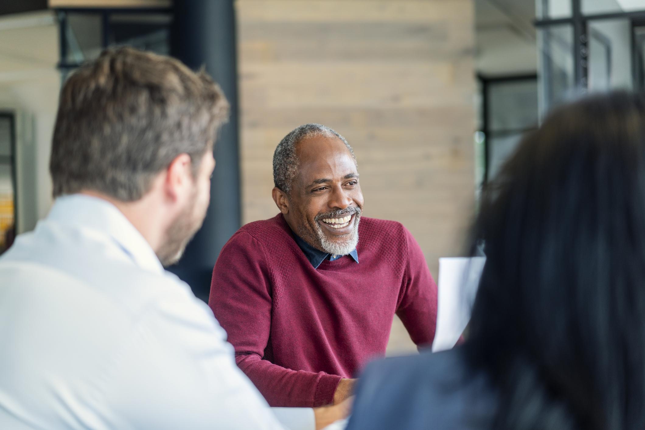 Homem sorrindo sentado com colegas em uma sala