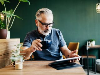 Man drinking a coffee while using a tablet