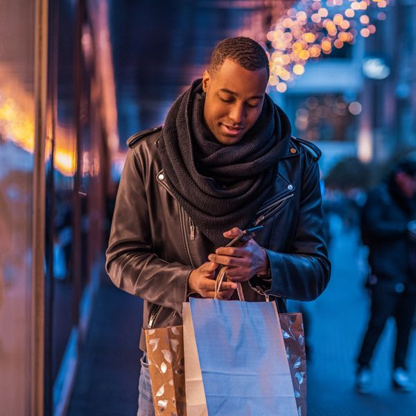 Man wearing winter clothes standing on a street holding paper bags and using a smartphone