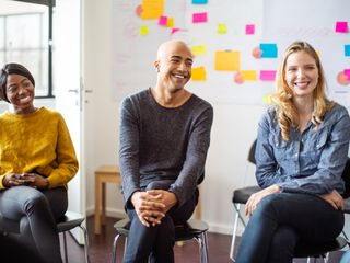 Multi-ethnic people sitting and smiling while having a meeting in the office with sticky notes on the wall
