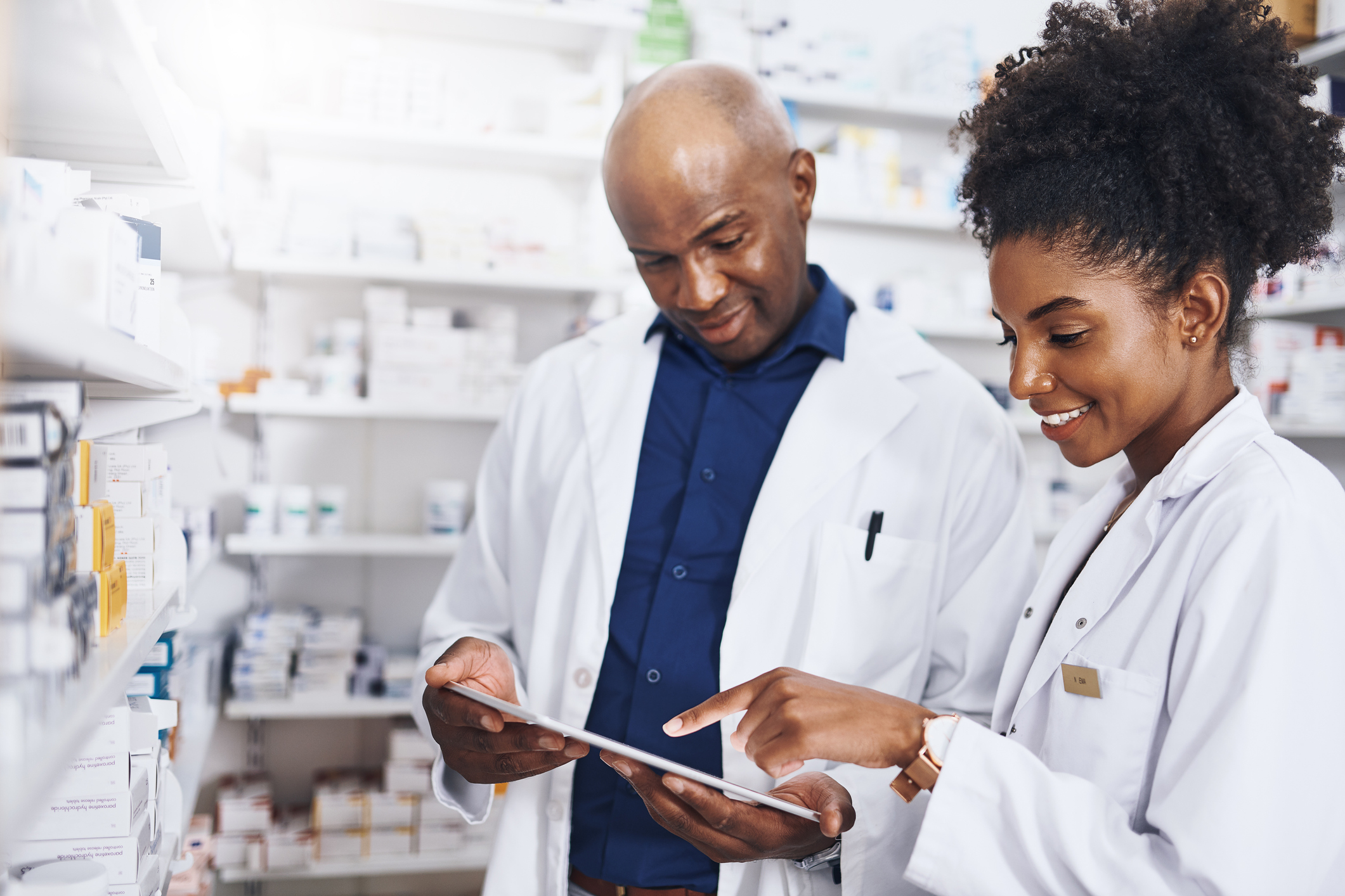 Two pharmacists doing inventory in a pharmacy with a digital tablet