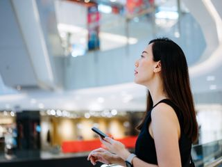 Woman using smartphone while shopping in a mall
