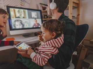 Man having video conference at home with his children around
