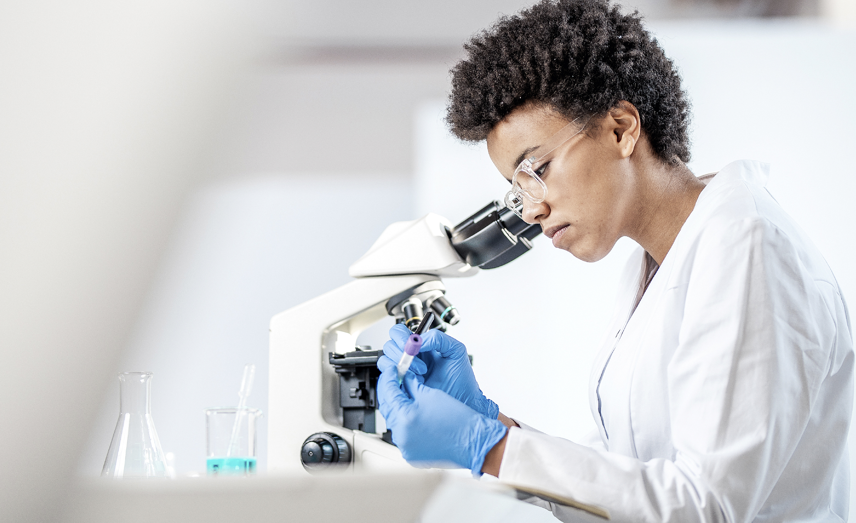 woman in a lab working on a microscope and marking a test tube