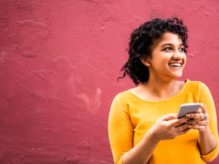 Pessoa usando telefone celular e sorrindo