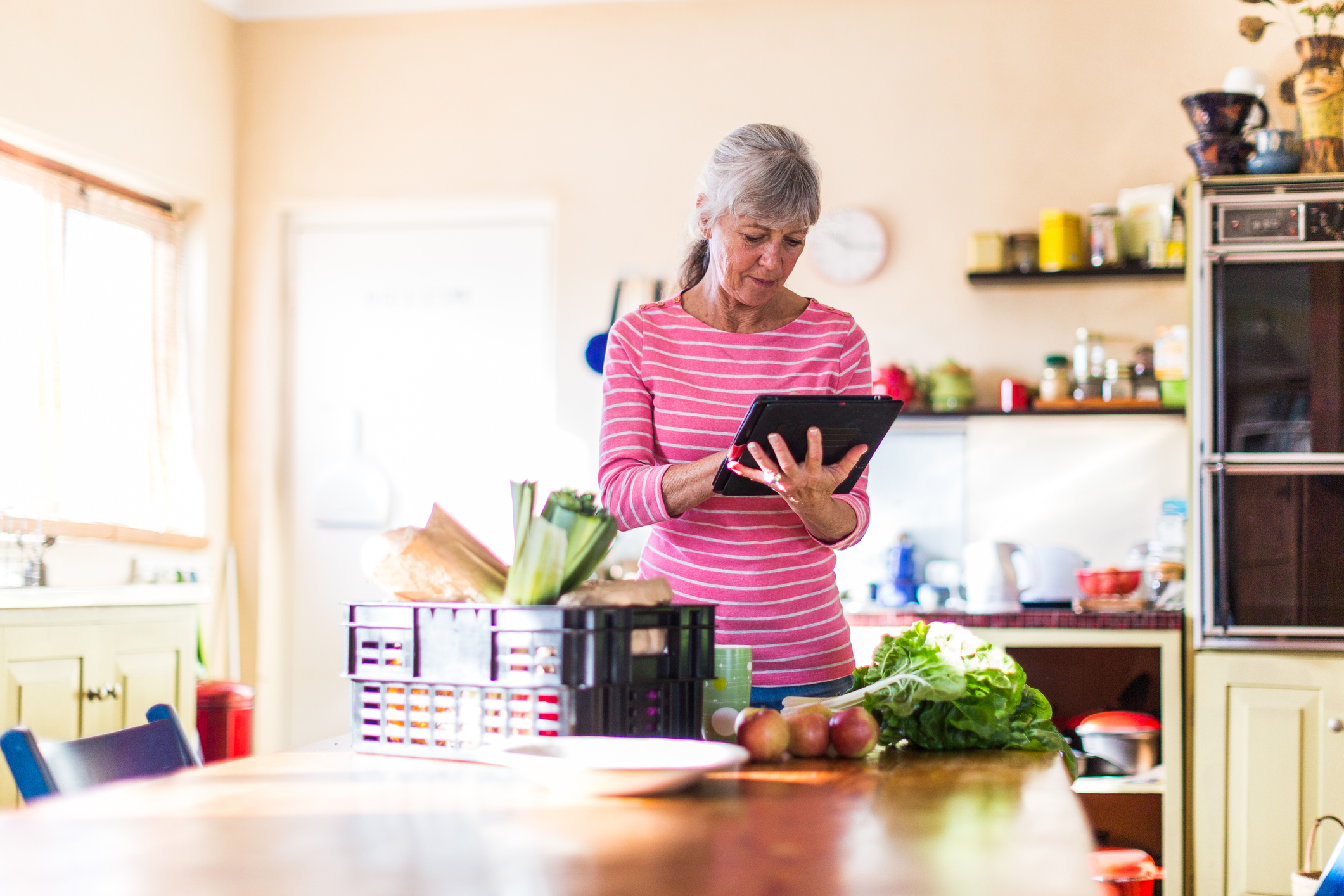Woman at kitchen checking groceries on tablet