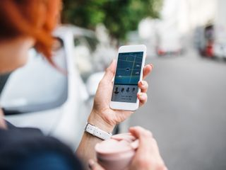 A woman looking at a ride sharing app on her phone