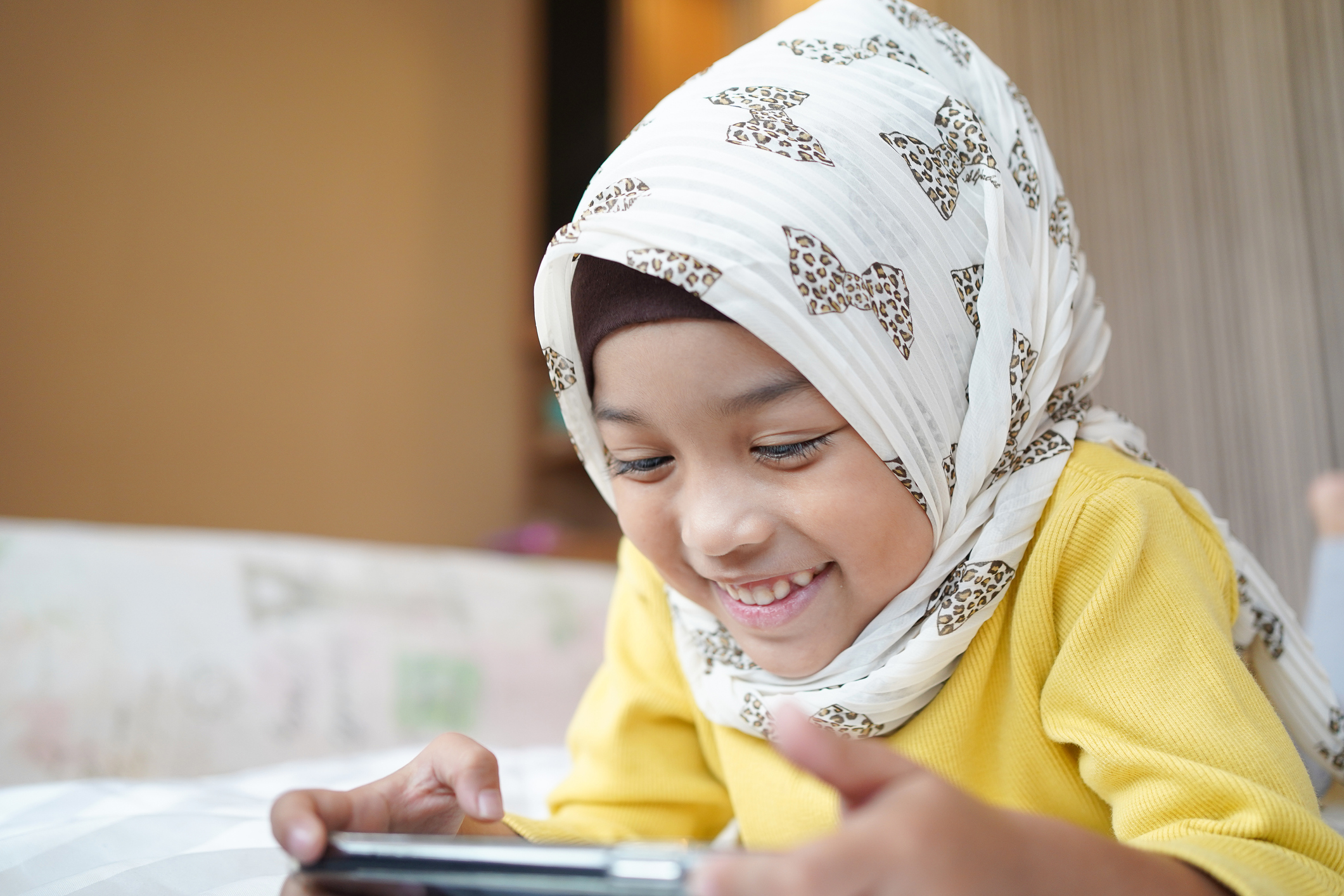 Asian Muslim child girl playing a smartphone at home