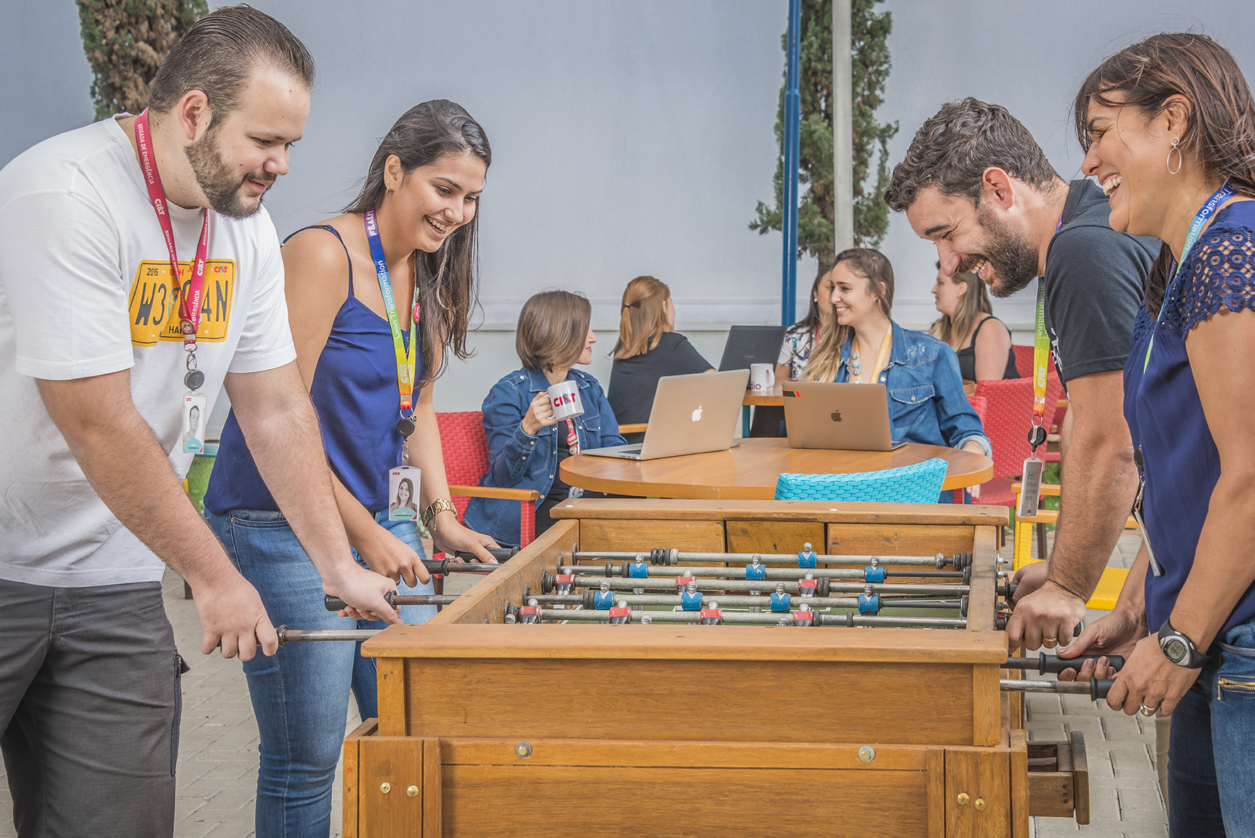 CI&T employees playing foosball while others are sitting on tables working in the back of the room