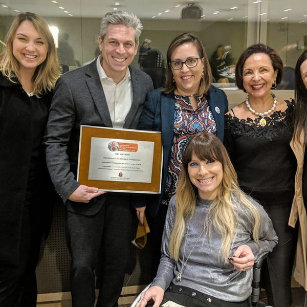 CI&T employees smiling including CI&T President Bruno Guicardi holding an award from the United Nations