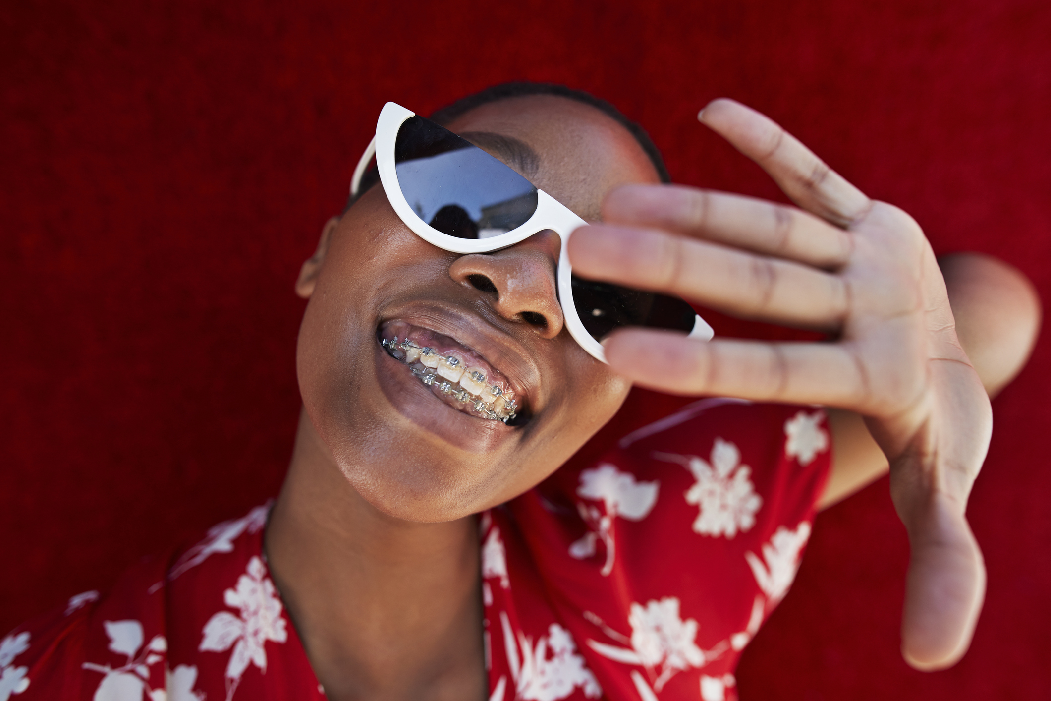 Close-up of smiling woman with braces with her hand up