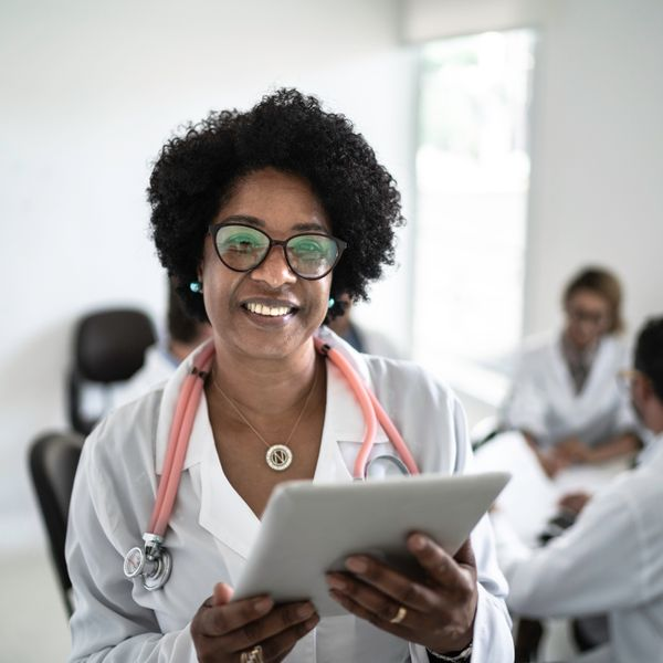 Female doctor using a digital tablet with doctor's meeting on background