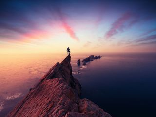 Man at the top of a mountain looking over the sea during sunset