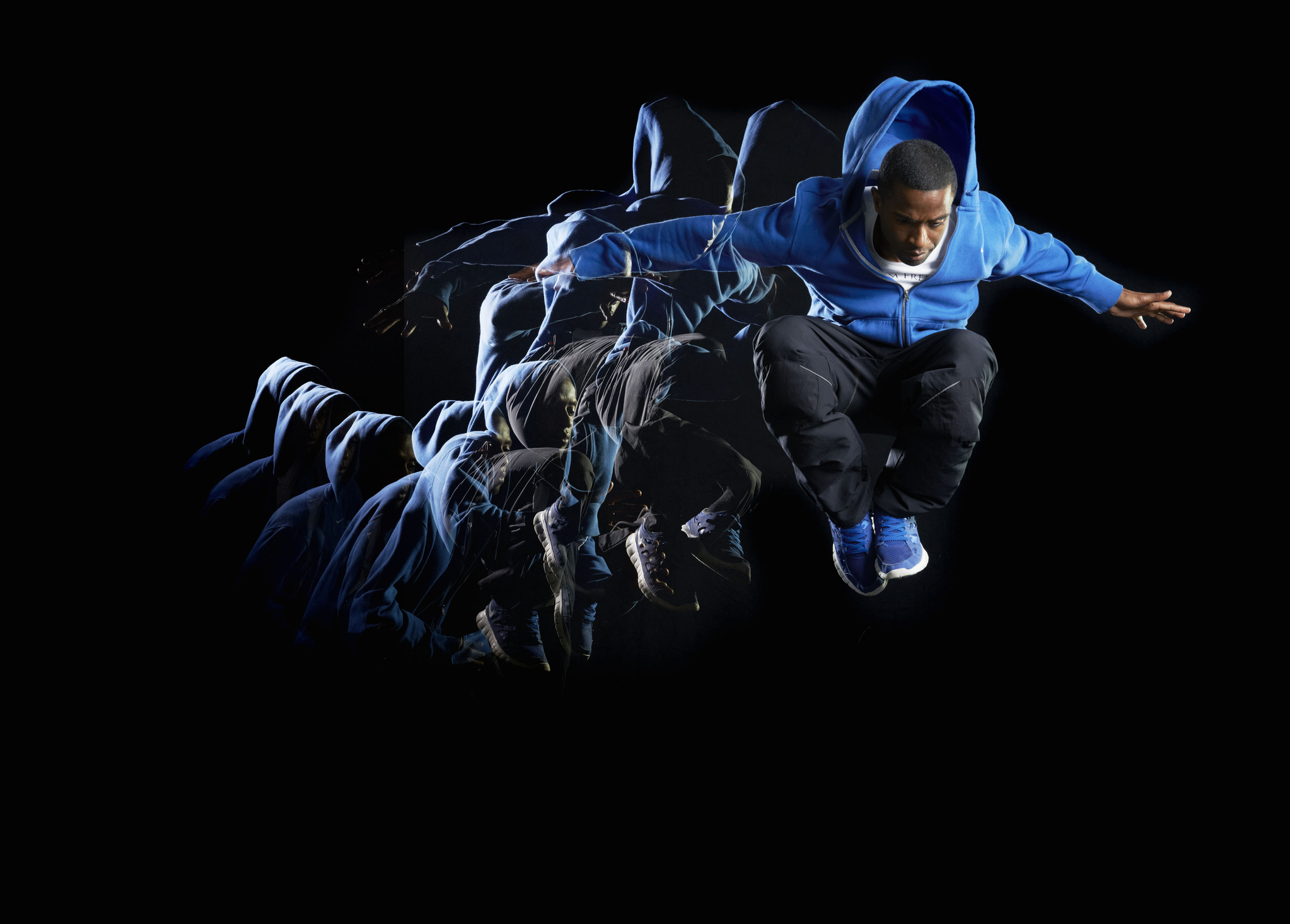 Man with blue jacket jumping in air with multiple strobe on a dark background