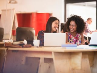 Two women smiling and working on a conference table