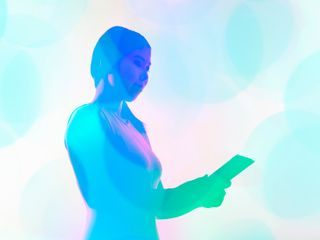 Woman holding a tablet with a blue filter