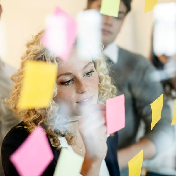 Woman in office behind glass pane with adhesive notes