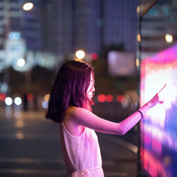 Woman using touch screen on the street