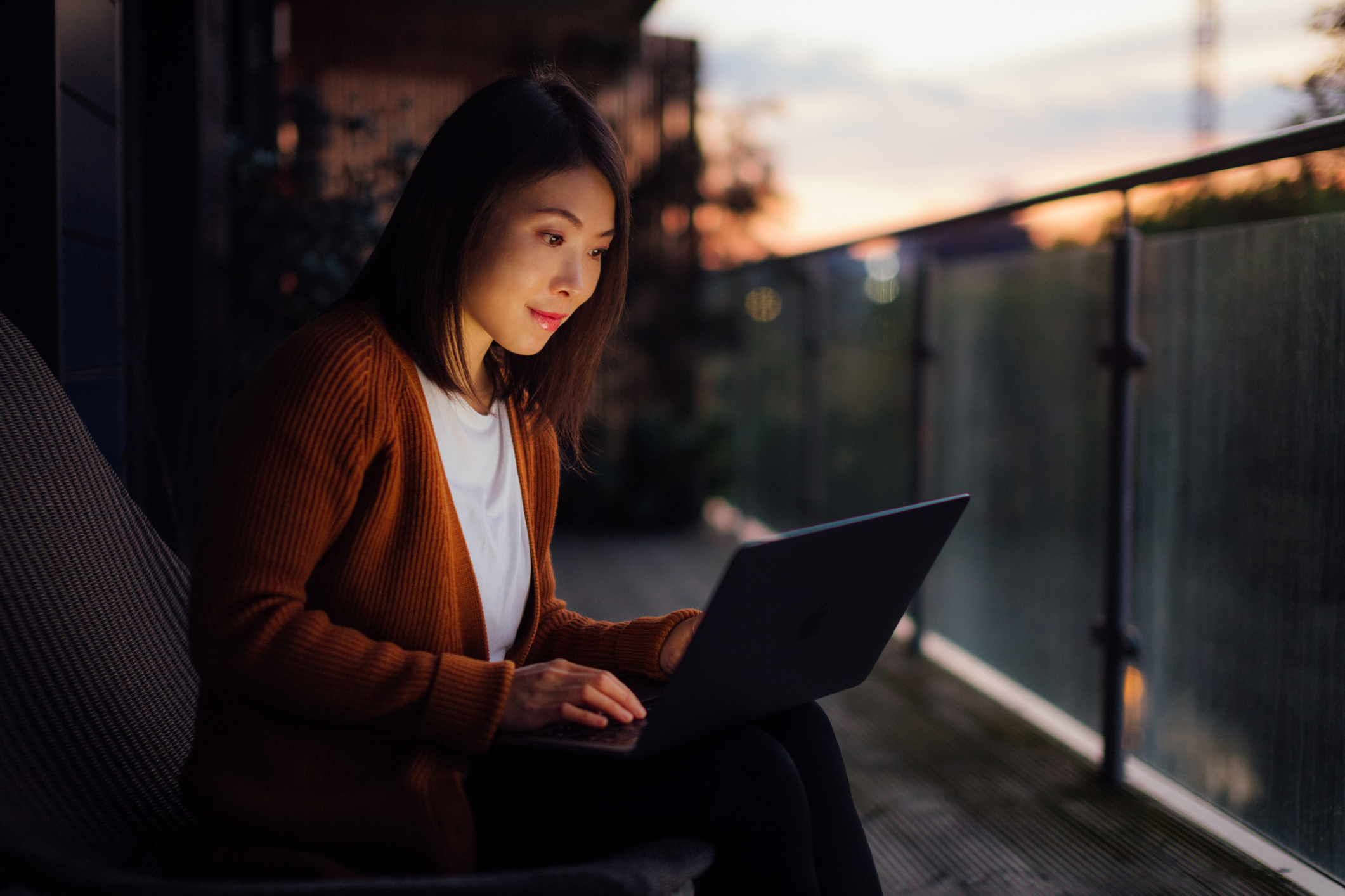 Woman working sitting on the balcony at night with a computer on her lap